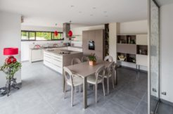 L'espace cuisine repas est résolument ouvert sur l'extérieur grâce aux grandes baies vitrées qui apportent aussi beaucoup de luminosité à la pièce