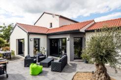 La couleur brique des tuiles de la toiture se marie parfaitement avec le gris anthracite des menuiseries extérieurs et des gouttières et donnent du caractère à la construction