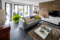 Le grand salon s'ouvre directement sur le jardin grâce aux grandes baies vitrées qui apportent aussi de la luminosité à la pièce