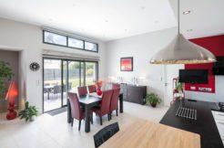 Espace cuisine salle à manger de la maison individuelle avec ouverture sur la terrasse et le jardin.
