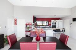 Cuisine ouverte sur la salle à manger avec mobilier de qualité et mur de couleur