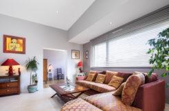 Pièce à vivre lumineuse grâce aux grandes ouvertures et utilisation d'un mobilier de qualité pour apporter du caractère à l'ensemble