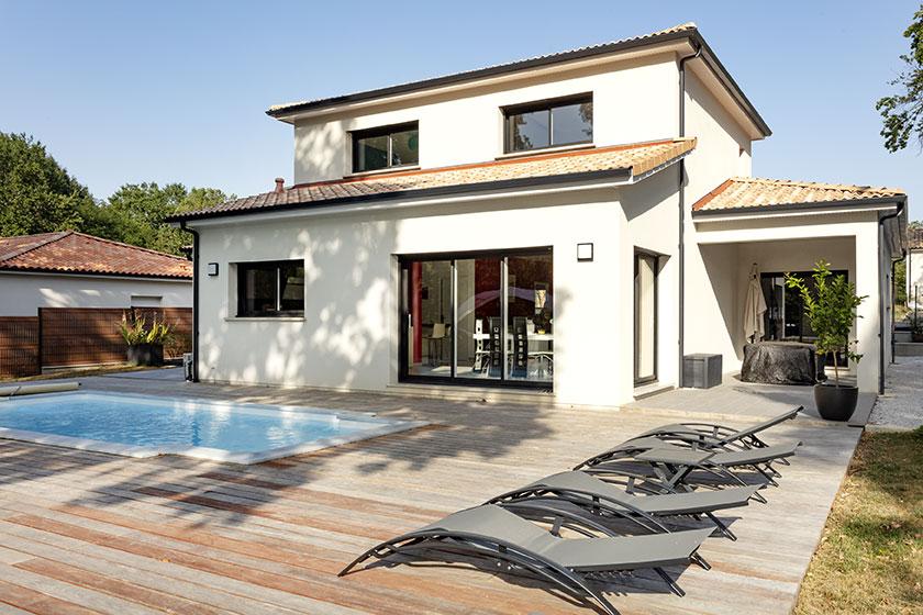 Maison à étage avec sa terrasse bois et sa piscine