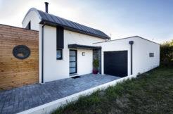 Façade de maison avec porte d'entrée, garage et séparateur en bois