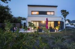 Maison à étage avec terrasse à la tombée de la nuit