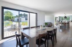 Une salle à manger lumineuse avec accès direct sur le salon, la cuisine et la terrasse
