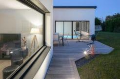 La terrasse longe la pièce de vie et permet d'accéder à la piscine