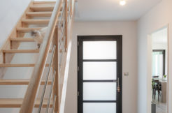 Un hall d'entrée avec un escalier en bois et un accès à l'espace de vie