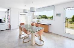 Salle à manger lumineuse avec accès direct au salon, à la cuisine et à la terrasse